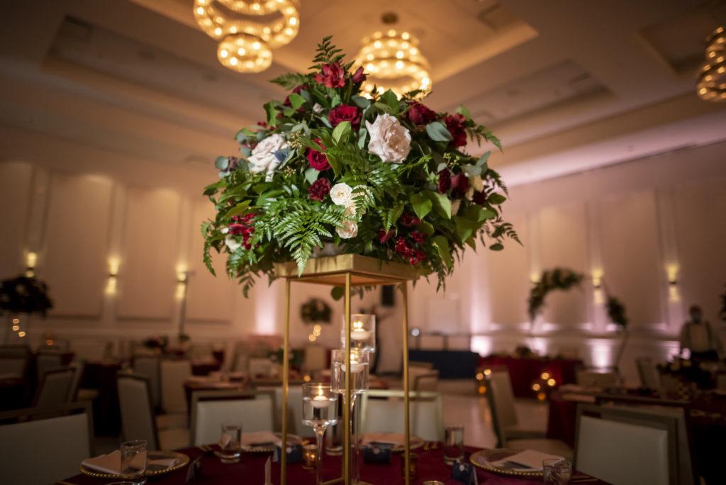 Elegant Wedding Reception Decor, Gold Stand with Greenery and Burgundy, Blush Pink Roses Floral Centerpiece   Tampa Bay Wedding Planner Coastal Coordinating   Wedding Rentals Kate Ryan Event Rentals