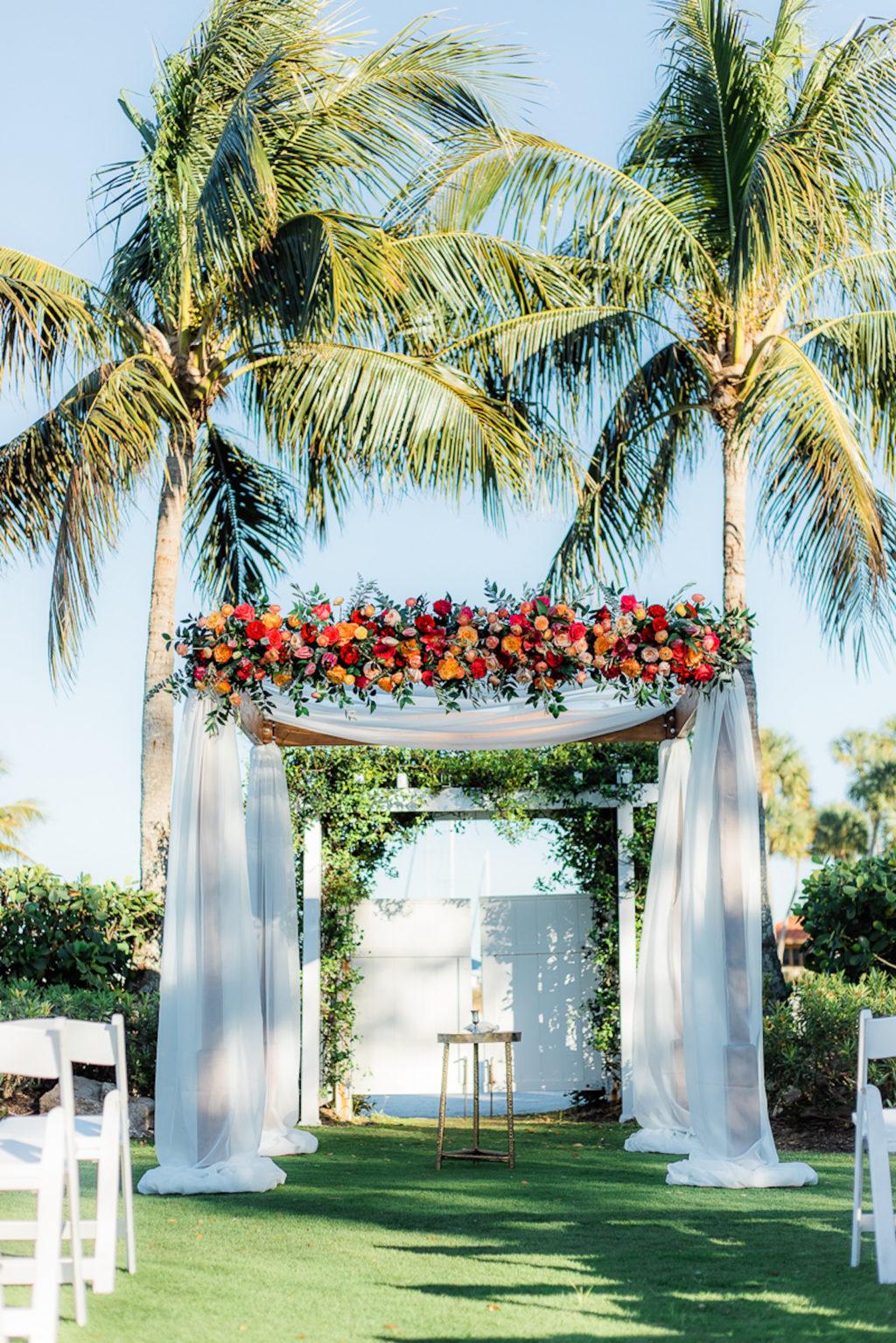 Elegant Wedding Ceremony Decor, Arch with White Linens Jewel Tone Orange, Pink, Red, Purple Roses, Greenery Floral Arrangements