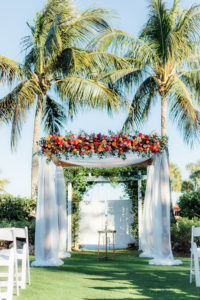 Elegant Wedding Ceremony Decor, Arch with White Linens Jewel Tone Orange, Pink, Red, Purple Roses, Greenery Floral Arrangements   The Resort at Longboat Key Club