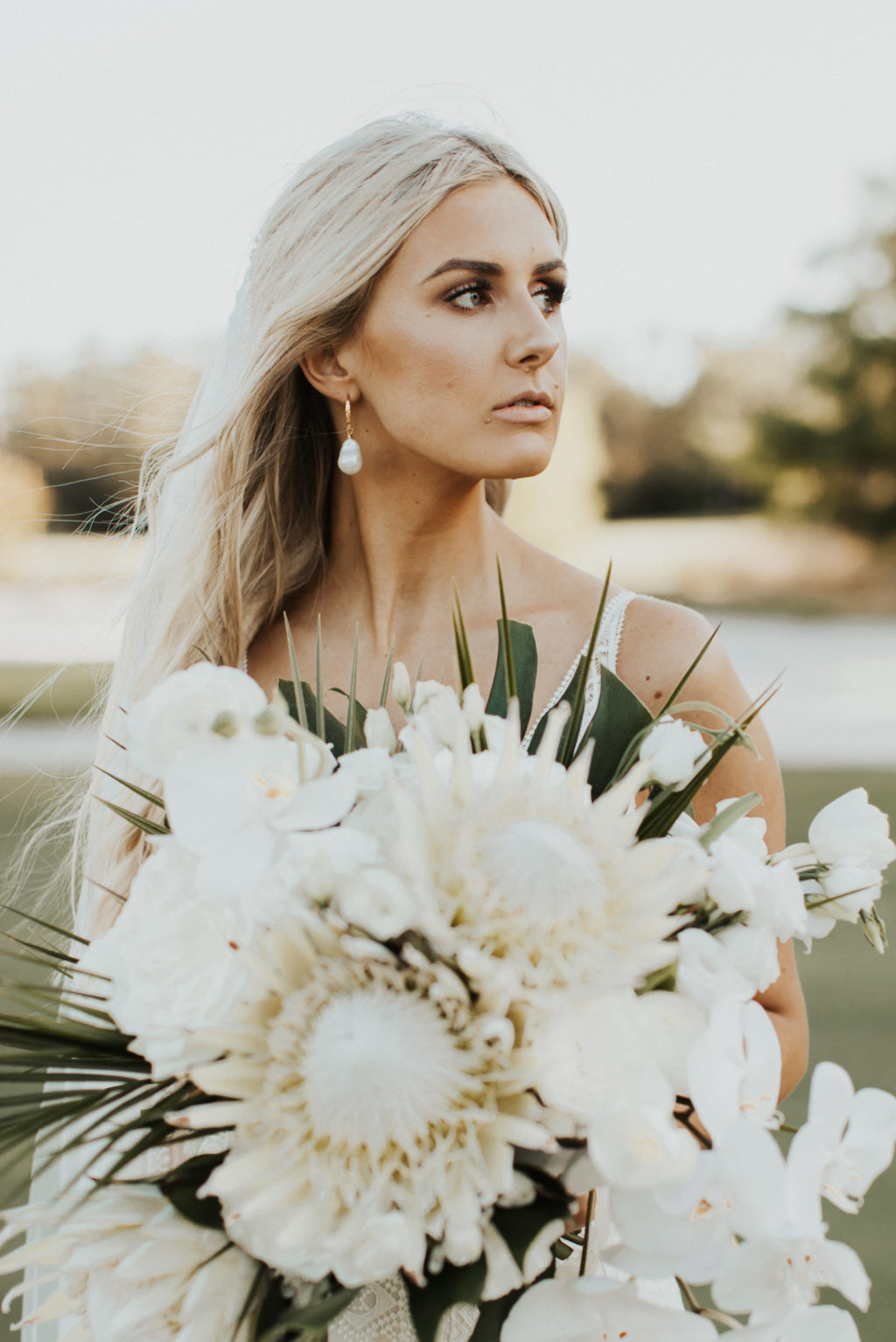 Timeless Bride Holding Lush Neutral Floral Bouquet, King Proteas, White Orchids, Palm Fronds