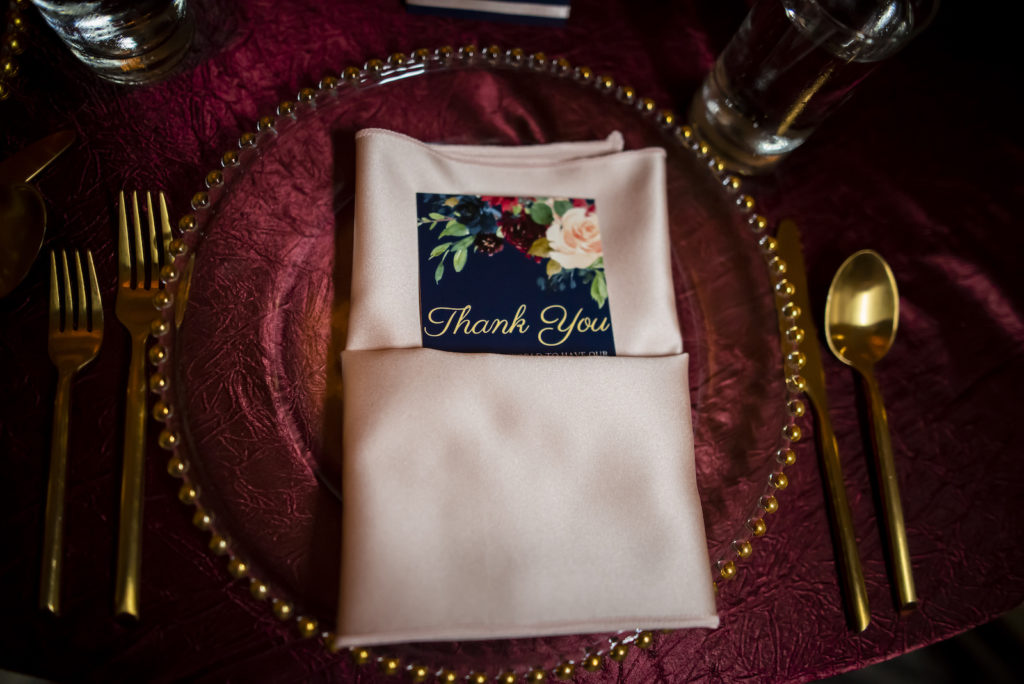 Elegant Wedding Reception Decor, Tabled with Burgundy Linen Tablecloth, Gold Silverware, Gold Beaded and Clear Glass Charger, Blush Pink Linen Napkin with Navy Blue and Floral Thank You Stationery   Tampa Bay Wedding Planner Coastal Coordinating