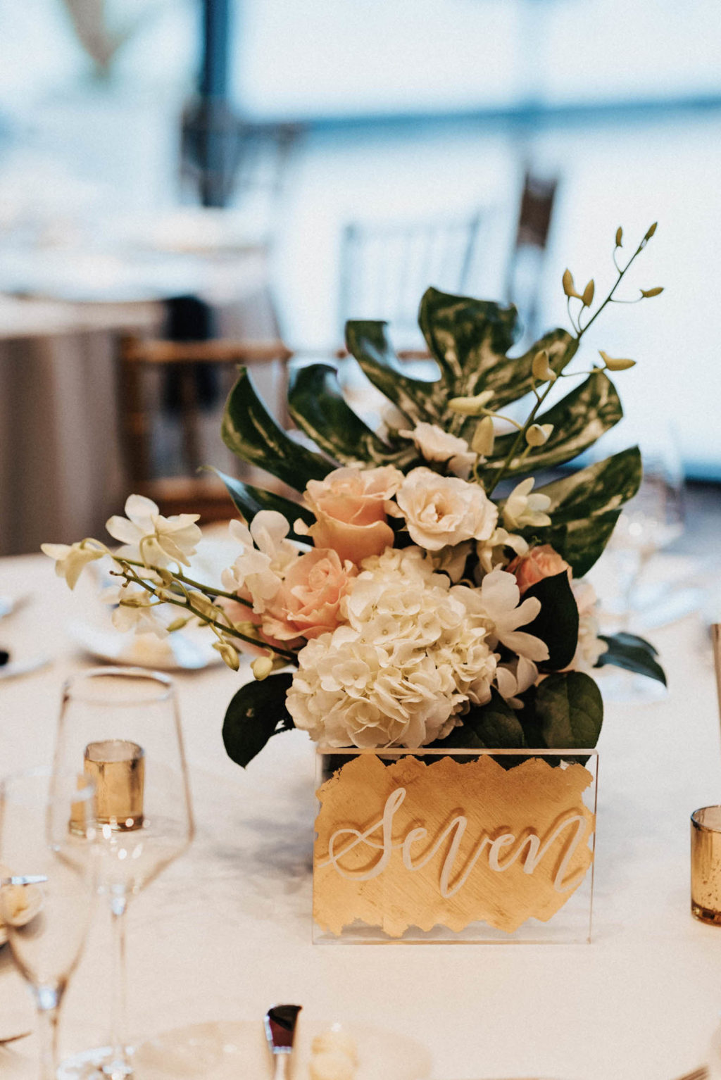 Gold Acrylic Table Numbers with Handwritten Writing | Blush and White Floral Centerpieces with Tropical Greenery