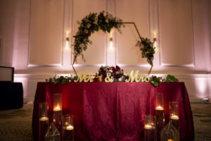 Burgundy and Gold Sweetheart Table with Geometric Arch Backdrop
