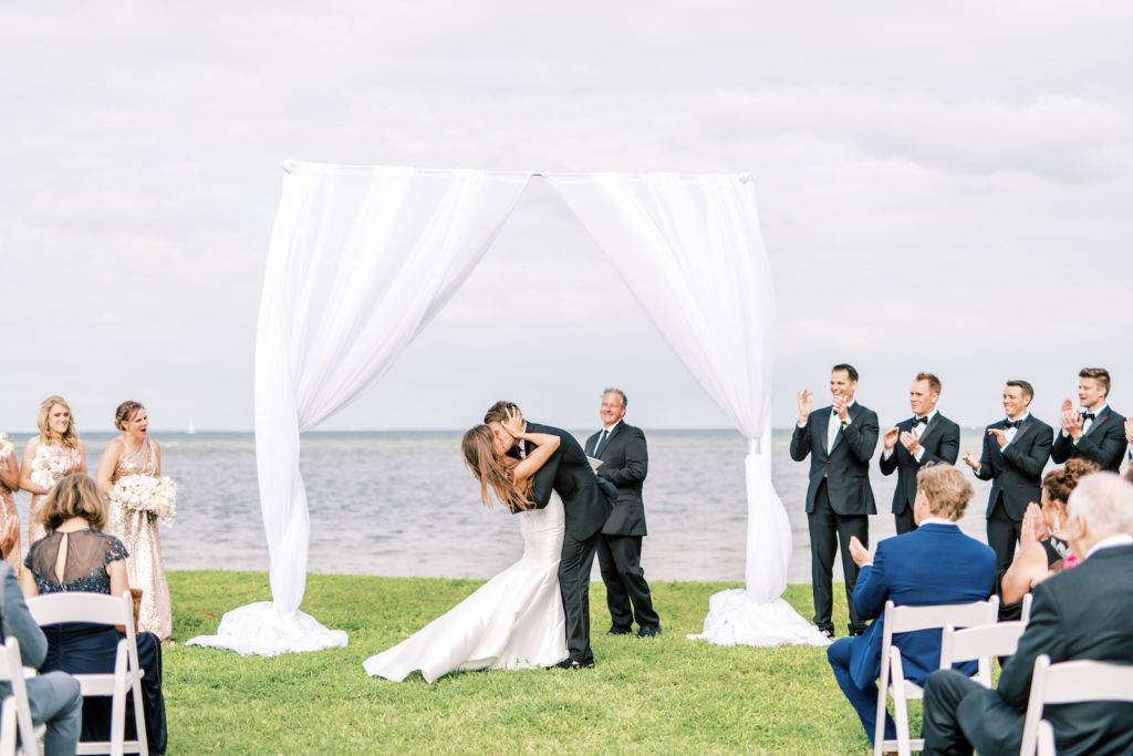 Florida Bride and Groom Exchange First Kiss Under Arch with White Linen Draping Outdoor Waterfront Wedding Ceremony | Tampa Bay Wedding Photographer Kera Photography