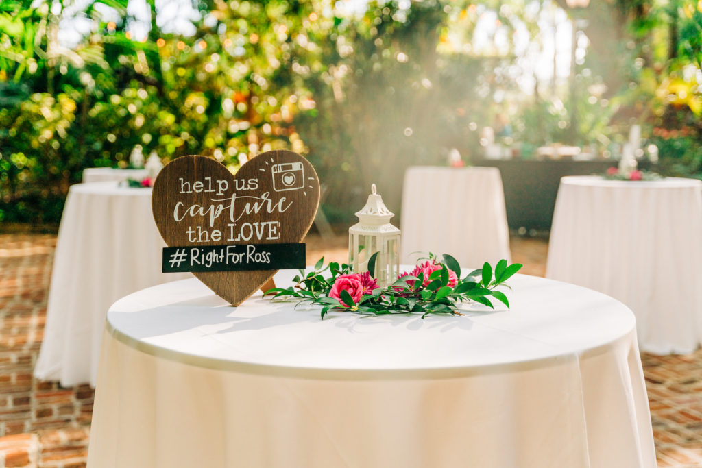 Rustic Wedding Cocktail Hour Décor | Hashtag Sign on White Linen and Circular Entrance Table | Vibrant Pink Centerpieces with Greenery