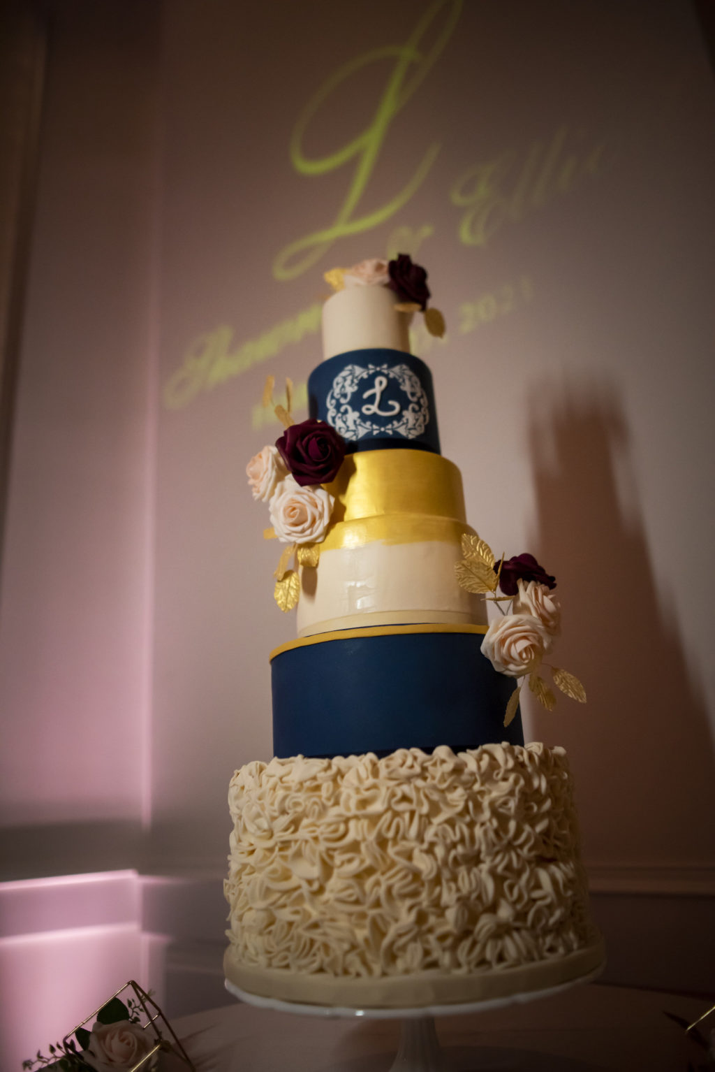 Six Tier Navy Blue, White, and Gold Round Wedding Cake with Monogram and Ruffled Tier   Dessert Inspiration