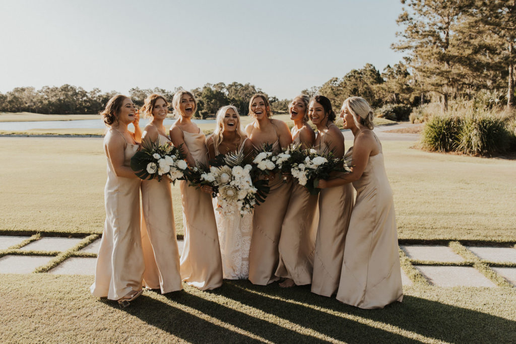 Neutral Timeless Bride with Bridesmaids in Silky Matching Champagne Gold Dresses Holding Floral Bouquets with White Roses and Palm Fronds   Tampa Bay Wedding Venue The Concession Golf Course