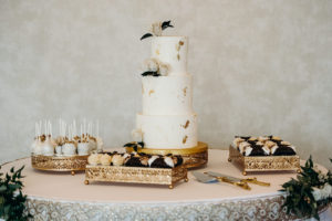 Elegant Three Tier White Wedding Cake with Gold Foil Specks, Ivory Roses, Cake Pops, Cannoli Desserts