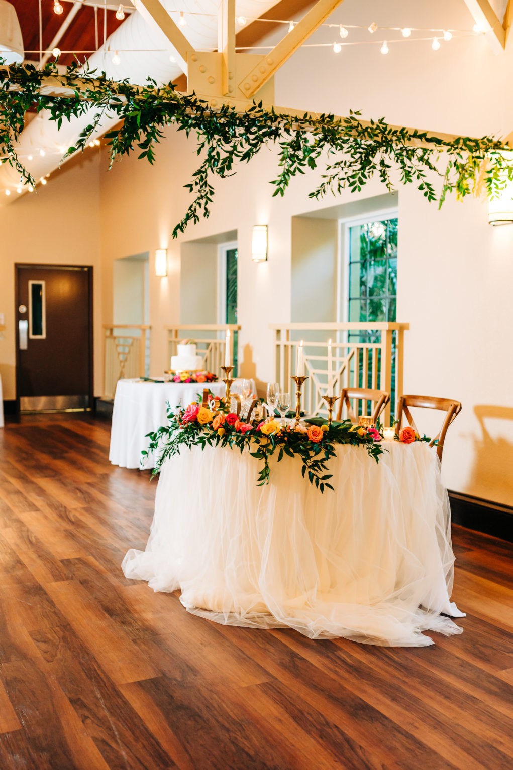 Garden Style Wedding Reception Décor Inspiration | White Linen and Circular Table with Wooden Chairs and Hanging Greenery | Vibrant Pink, Yellow, and Orange Centerpieces | Sweetheart Table Ideas