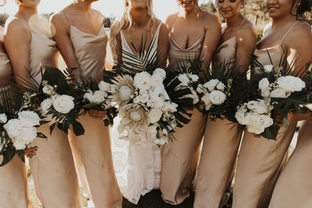 Neutral Timeless Bride with Bridesmaids in Silky Matching Champagne Gold Dresses Holding Floral Bouquets with White Roses, King Proteas, Monstera Palm Leaves, White Orchids and Palm Fronds