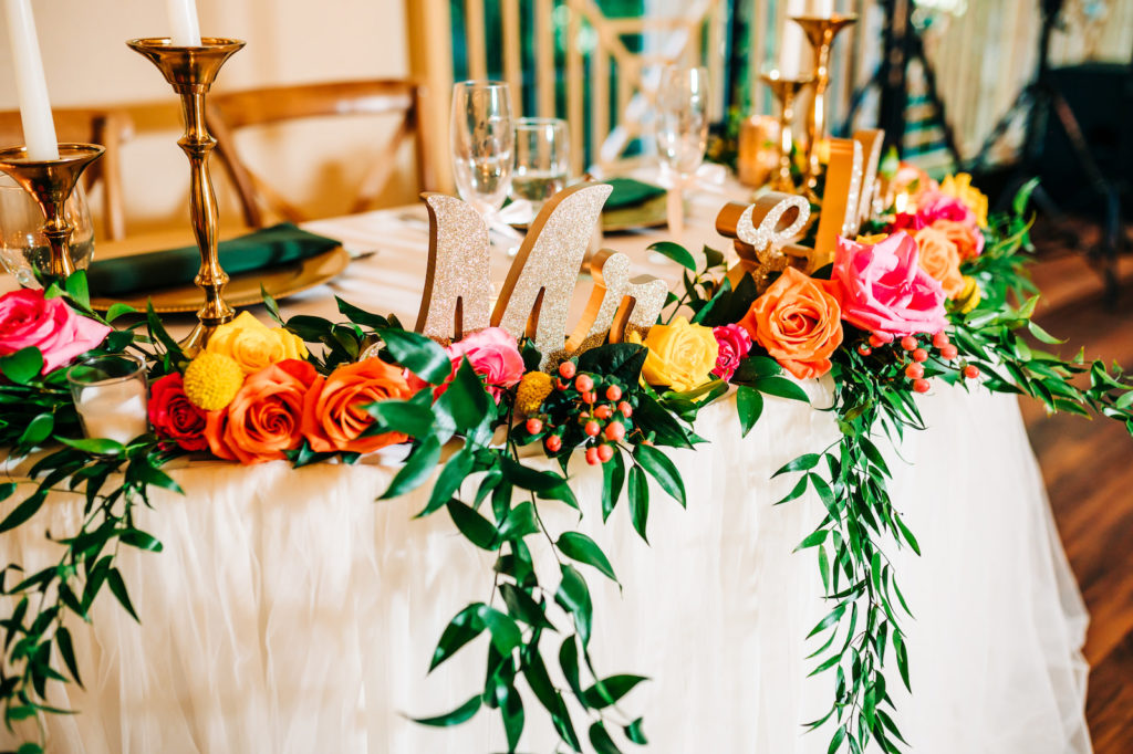 Sweetheart Table with Wooden Chairs and Hanging Greenery | Vibrant Pink, Yellow, and Orange Rose Centerpieces | Garden Style Wedding Reception Décor Ideas