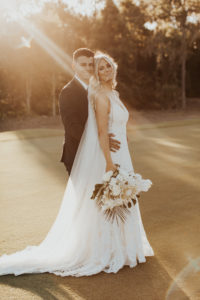 Timeless Groom Holding Bride from behind   Bride Holding Lush Neutral Floral Bouquet, White Orchids, King Proteas, Palm Fronds, Monstera Palm Leaves