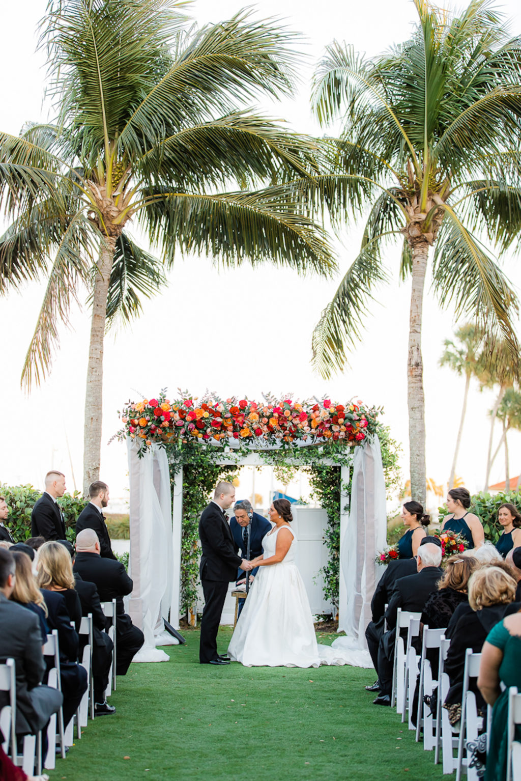 Elegant Waterfront Outdoor Garden Wedding Ceremony Decor, Bride and Groom Exchanging Wedding Vows, White Folding Chairs, Tall Wooden Aisle Pedestals with Jewel Tone Floral Arrangements, Arch with White Linens and Flowers | Tampa Bay Wedding Venue The Resort at Longboat Key Club