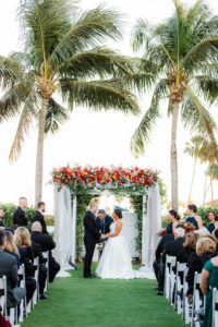 Elegant Waterfront Outdoor Garden Wedding Ceremony Decor, Bride and Groom Exchanging Wedding Vows, White Folding Chairs, Tall Wooden Aisle Pedestals with Jewel Tone Floral Arrangements, Arch with White Linens and Flowers   Tampa Bay Wedding Venue The Resort at Longboat Key Club