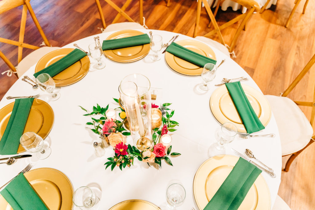 Green and Gold Wedding Place Settings with Vibrant Bright Pink Flowers and Greenery Candle Centerpiece | Wooden Chairs and White Linens | Rustic Garden Reception Decor Inspiration