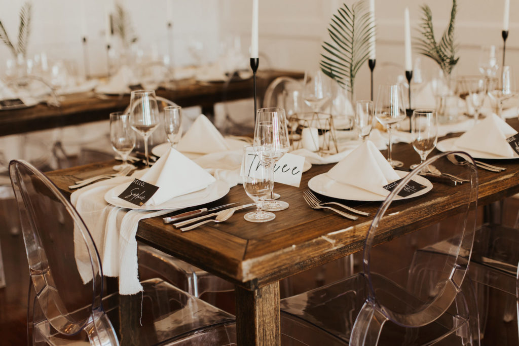 Neutral Timeless Wedding Reception Decor, Long Wooden Feasting Table, Acrylic Ghost Chairs, Simple One Leaf Palm Frond in Vases, Tall Black Candlesticks, Geometric Candle Holders, White Linen Table Runner