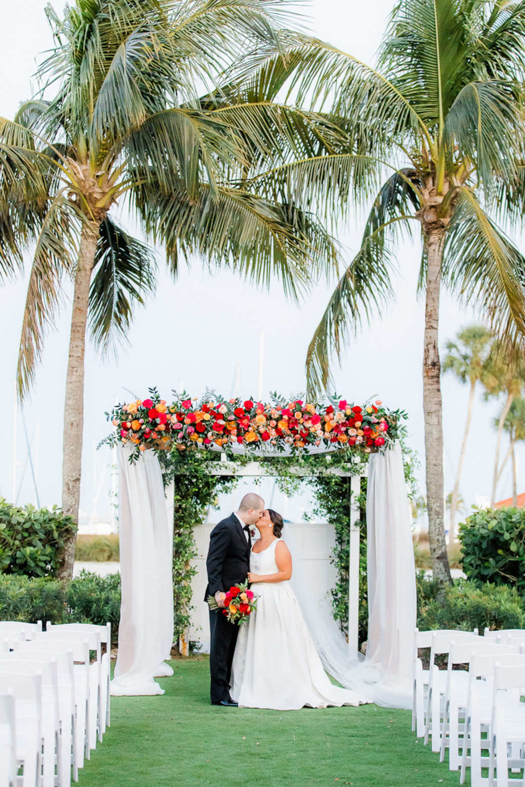 Florida Bride and Groom Kissing Under Wedding Ceremony Arch with White Linens with Colorful Jewel Tone Pink, Orange, Red Flowers and Greenery | Tampa Outdoor Waterfront Garden Wedding Venue The Resort at Longboat Key Club