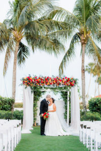 Florida Bride and Groom Kissing Under Wedding Ceremony Arch with White Linens with Colorful Jewel Tone Pink, Orange, Red Flowers and Greenery   Tampa Outdoor Waterfront Garden Wedding Venue The Resort at Longboat Key Club