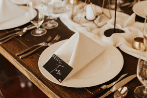 Timeless Neutral Wedding Reception Decor, White Plate with Linen Napkin, Black Name Card on Wooden Table