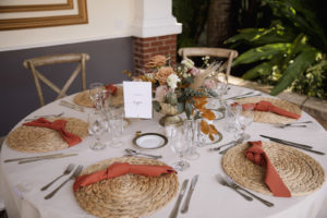 Wicker Place Mats with Burnt Orange Napkins on Cream Linen | Low Centerpieces with Roses, Greenery, and Pampas Leaves in Gold Holder | Bohemian Wedding Reception Decor | Sarasota Kate Ryan Event Rentals