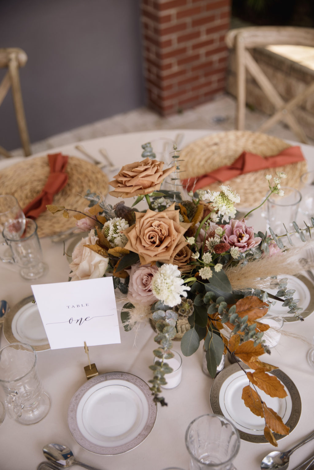 Wicker Place Mats with Burnt Orange Napkins on Cream Linen   Low Centerpieces with Roses, Greenery, and Pampas Leaves in Gold Holder   Bohemian Wedding Reception Decor for Tablescapes   Sarasota Rentals Kate Ryan Event Rentals