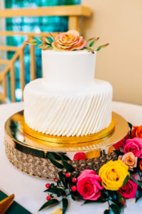 White Two Tiered Wedding Cake with Texture Layer | Gold Cake Stand and Floral Bright Cake Topper