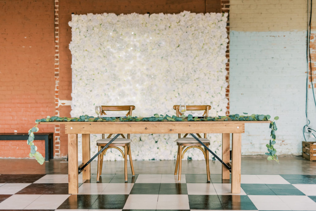 Simple Wedding Reception Decor, Wooden Long Table with Greenery Garland, Wooden Cross Back Chairs, White Floral Backdrop, Black and White Checkered Dance Floor | Tampa Bay Wedding Photographer Kera Photography | Wedding Rentals Gabro Event Services