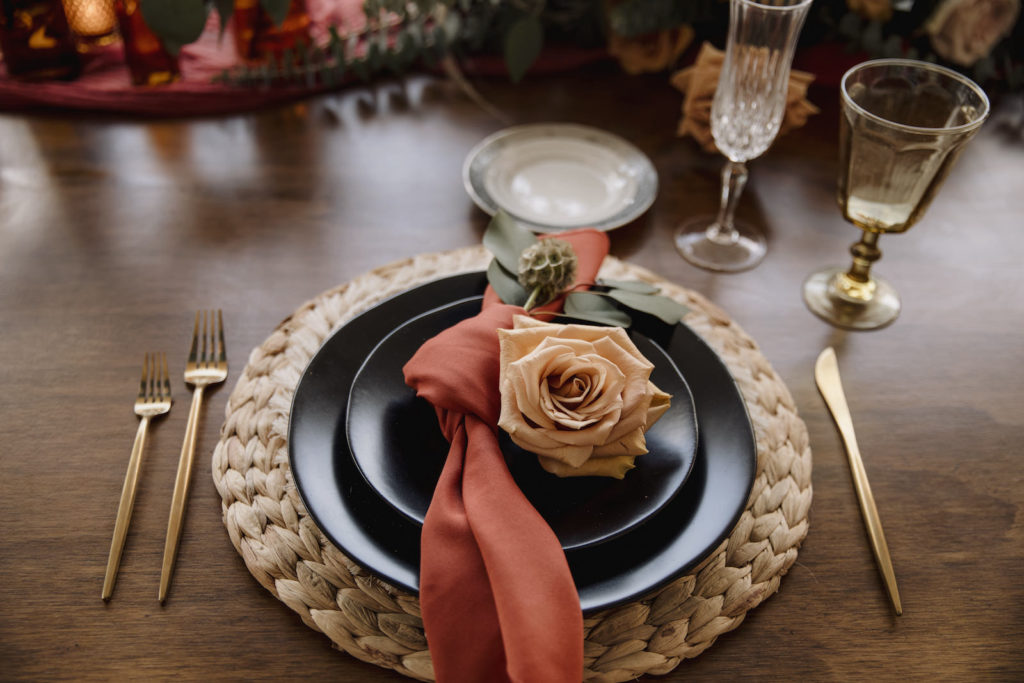 Wicker Placemat with Black Dishes Place Setting and Burnt Orange Napkins, Gold Flatware, and Rose Flower   Boho Wedding Reception Decor and Ideas