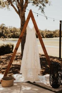 Romantic Flowy Lace Wedding Dress Hanging on Wooden Triangular Arch   Bradenton Wedding Venue The Concession Golf Club