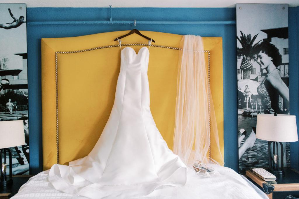 Classic Crepe Strapless Wedding Dress Hanging on Yellow Bed Headboard | Tampa Bay Wedding Photographer Kera Photography
