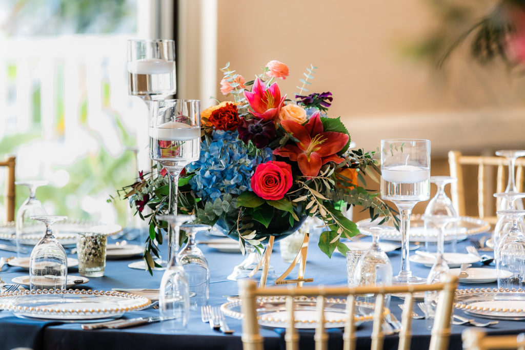 Elegant Wedding Reception Decor, Floating Candlesticks, Low Floral Centerpiece, Blue Hydrangeas, Red and Orange Roses, Pink Tropical Flower, Gold Laser Cut Table Number