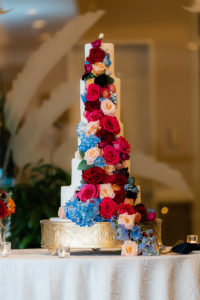Elegant Five Tier White Wedding Cake with Cascading Blue Hydrangeas, Red and Blush Pink Roses