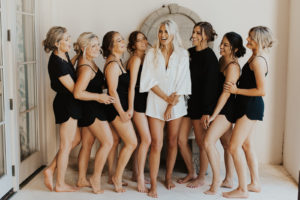 Bride in White Romper with Bridesmaids in Black Pajamas Getting Wedding Ready