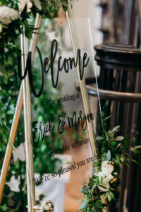 Modern Acrylic with Black Font Welcome Wedding Signage, White Roses and Greenery Arrangements