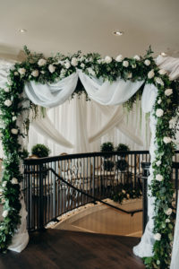 Elegant Timeless Wedding Ceremony Decor, Arch with White Linen Draping, Greenery Garland with White Roses on Top of Staircase | Tampa Bay Wedding Venue Westshore Yacht Club