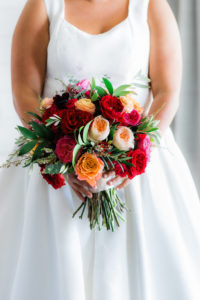 Tampa Bride Wearing A-Line Wedding Dress Scoop Neckline Holding Jewel Tone Pink, Red and Coral Roses with Greenery Floral Bouquet
