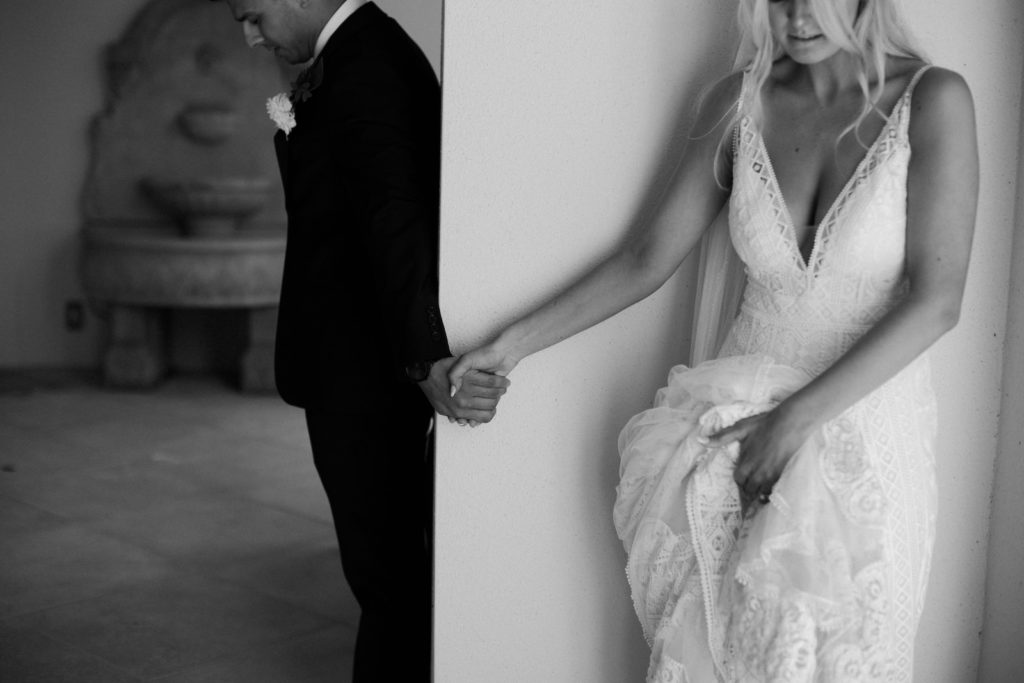 Unique Bride and Groom Holding Hands Behind Wall Secret First Look Wedding Photo