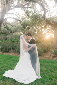 Bride and Groom Veil Shot Wedding Portrait   Bride in BHLDN Illusion Back Ballgown with Classic Updo and Natural Makeup   Tampa Bay Hair and Makeup Artist Femme Akoi Beauty Studio