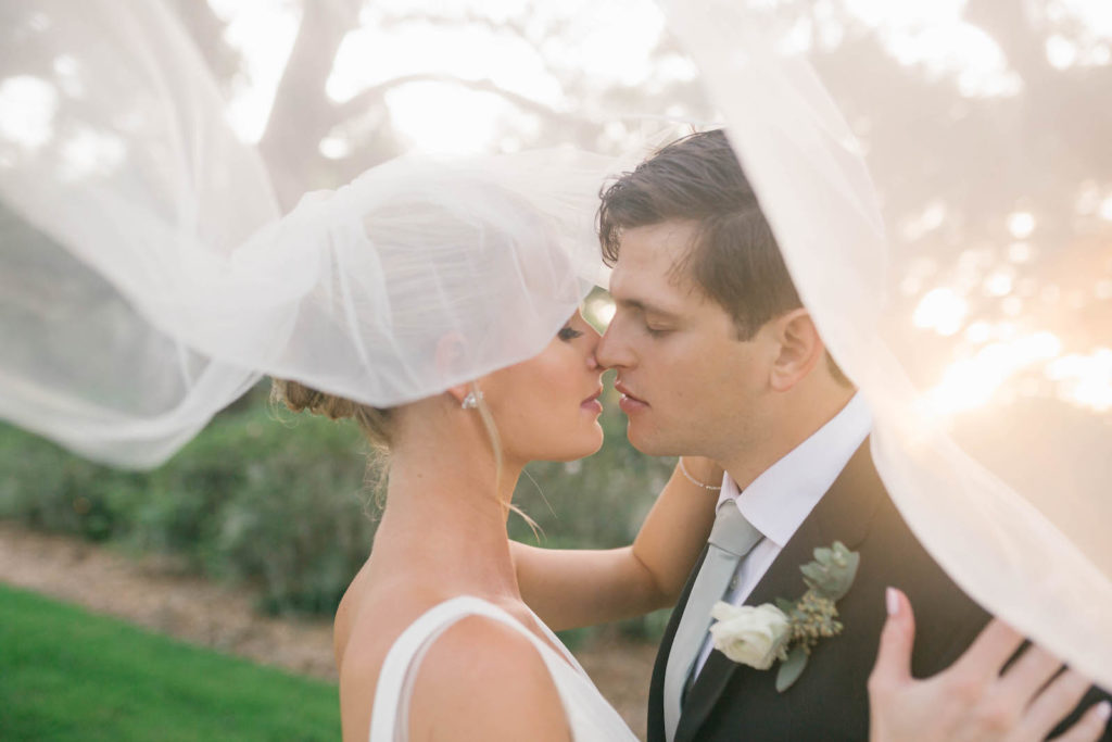 Bride and Groom Veil Shot Wedding Portrait | Bride in BHLDN Illusion Back Ballgown with Classic Updo and Natural Makeup | Tampa Bay Hair and Makeup Artist Femme Akoi Beauty Studio