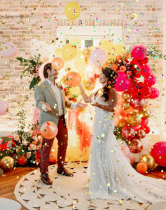 Whimsical and Colorful Bride and Groom Gold Confetti Photo with Orange, Pink, Yellow and Gold Balloon and Fringe Ceremony Backdrop | Tampa Bay Wedding Photographer Dewitt for Love | St. Pete Modern Industrial Wedding Venue Red Mesa Events