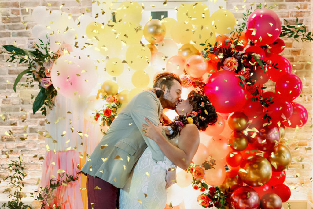 Whimsical and Colorful Groom Dip Kissing Bride with Gold Confetti Photo with Orange, Pink, Yellow and Gold Balloon and Fringe Ceremony Backdrop   Tampa Bay Wedding Photographer Dewitt for Love   St. Pete Modern Industrial Wedding Venue Red Mesa Events
