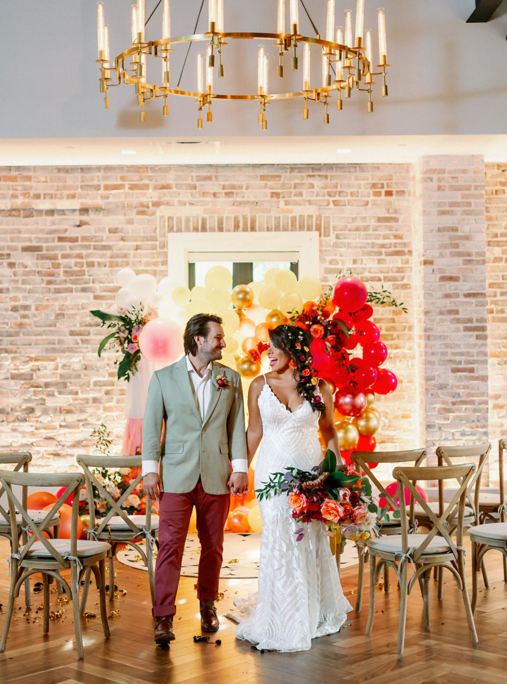 Bride and Groom Holding Hands, Whimsical and Colorful Wedding Decor, Yellow, Pink, Orange, White, Gold Fringe and Balloon Ceremony Backdrop, Wooden Cross Back Chairs, Gold and Candlestick Chandelier, White Brick Wall   Tampa Bay Wedding Photographer Dewitt for Love   St. Pete Modern Industrial Wedding Venue Red Mesa Events   Wedding Chair Rentals Kate Ryan Event Rentals