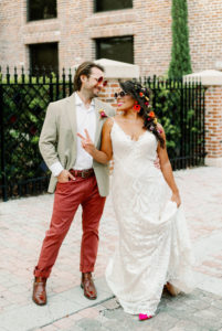 Whimsical Bride Wearing Lace Boho Spaghetti Strap and V Neckline Wedding Dress, Hair in Braid with Colorful Flowers and Sunglasses, Groom in Dusty Red Pants, Gray Suit Jacket and Red Retro Sunglasses | Tampa Bay Wedding Photographer Dewitt for Love