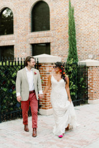 Whimsical Bride Wearing Lace Boho Spaghetti Strap and V Neckline Wedding Dress, Hair in Braid with Colorful Flowers and Sunglasses, Groom in Dusty Red Pants, Gray Suit Jacket and Red Retro Sunglasses | Tampa Bay Wedding Photographer Dewitt for Love | St. Pete Modern Industrial Wedding Venue Red Mesa Events