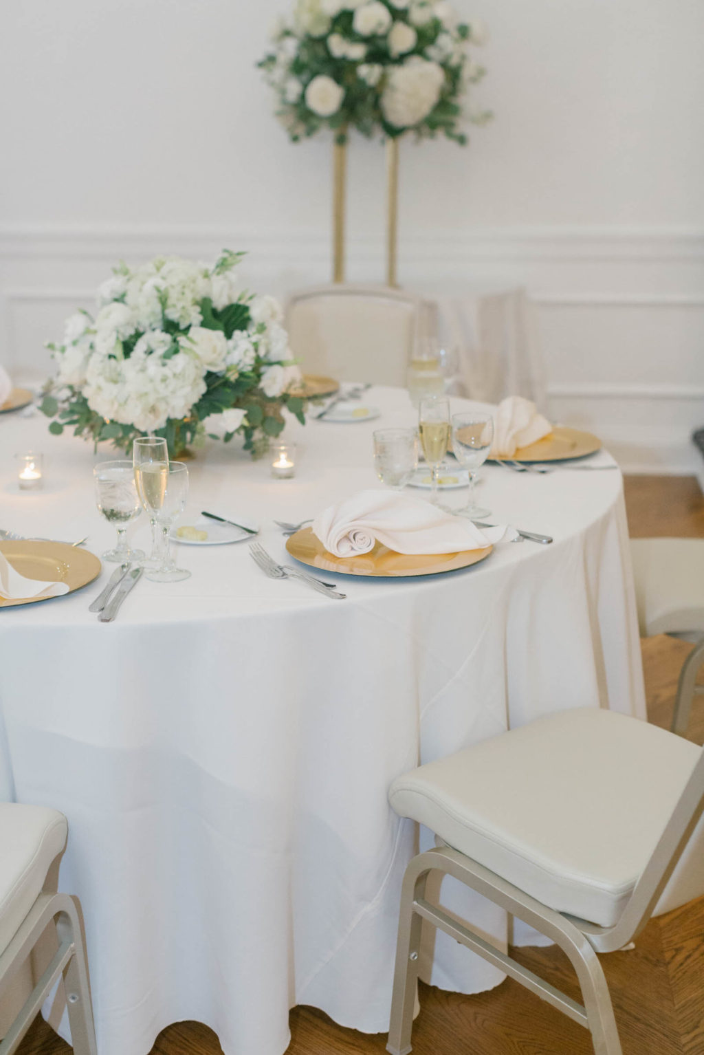 White Linen, Gold Chargers with White Napkins, White Rose and Greenery Centerpieces | Tampa Bay Wedding Florist FH Events