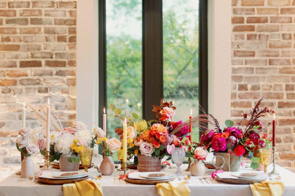 Whimsical Wedding Reception Tablescape Decor, Tall Yellow, Red and Orange Candlesticks, Colorful Floral Low Centerpieces, Blush Pink, and Red Roses, Yellow Pincushion Protea, White, Fuschia Flowers, Eucalyptus, Pampas Grass, Yellow Linen Napkins   Tampa Bay Wedding Photographer Dewitt for Love   St. Pete Modern Industrial Wedding Venue Red Mesa Events   Linen Rentals Kate Ryan Event Rentals