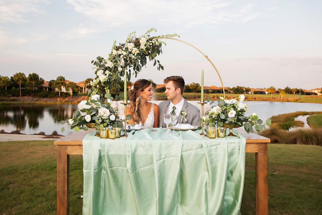 Bride and Groom Wedding Reception Photo | Outdoor Romantic Wedding Sweetheart Table Decor, Wooden Table, Ivory Tufted Loveseat, Gold Round Metal Arch with Floral Arrangement, White Anemone and Roses, Greenery, Eucalyptus, Sage Green Table Linen, Gold Mercury Votives, Gold Candlesticks and Sage Green Candles | Tampa Bay Wedding Photographer Limelight Photography | Wedding Planner MDP Events | Wedding Florist Beneva Florals | Wedding Venue Esplanade Country Club
