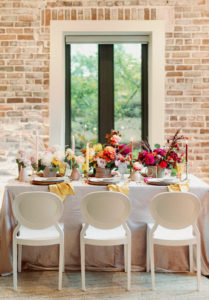 Whimsical and Colorful Wedding Reception Decor, White Dining Chairs, Yellow, Red and White Candlesticks, Colorful Flower Low Centerpieces | St. Pete Modern Industrial Wedding Venue Red Mesa Events | Tampa Wedding Photographer Dewitt for Love | Linen Rentals Kate Ryan Event Rentals