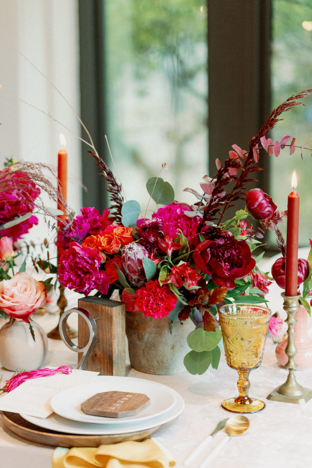 Whimsical and Colorful Wedding Reception Tablescape Decor, Fuschia and Pink, Red Low Floral Centerpiece, Eucalyptus, Tall Orange and Red Candlesticks, Yellow Vintage Glassware, Wooden Charger, Wood Geometric Shape Place Card   Tampa Bay Wedding Photographer Dewitt for Love   Linen Rentals Kate Ryan Event Rentals
