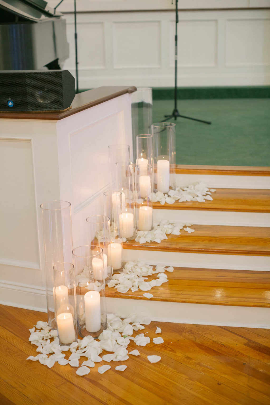 White Flower Petals Lining Church Wedding Aisle | White Candles in Tall Vases Adorning Wedding Aisle | Wedding Ceremony Decor